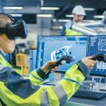 AVEVA Factory: Female Industrial Engineer Wearing Virtual Reality Headset and Holding Controllers, She Uses VR technology for Industrial Design, Development and Prototyping in CAD Software.